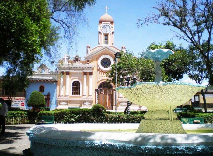Fuente en la plaza central con la iglesia de fondo