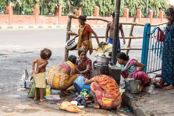 Familias se concentran alrededor de uno de los grifos en la calle para lavar los cacharros de la cocina