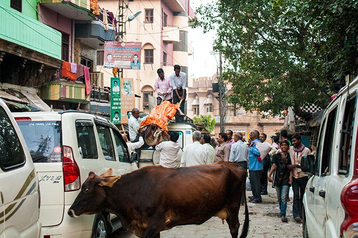 Bajando un cuerpo de la baca de un coche para llevarlo al Ghat crematorio