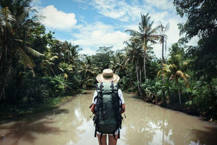 Chica exploradora navegando un río vía Shutterstock