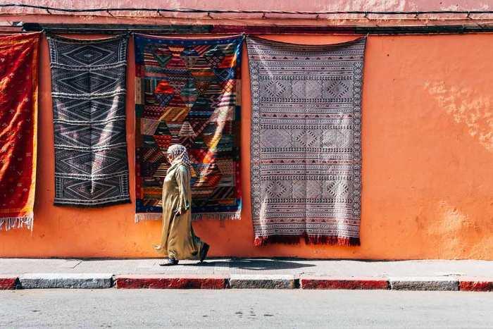 Mujer caminando por las calles de Marrakech junto a unas coloridas alfombras