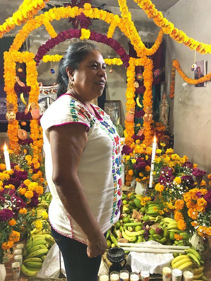 mujer frente altar del día de los muertos en santa fe de la laguna michoacan mexico