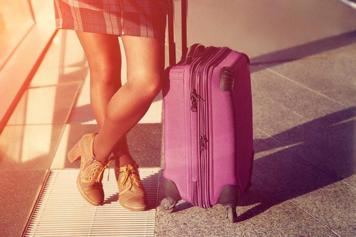 Mujer en aeropuerto con equipaje de mano
