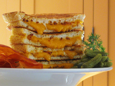 Grilled cheddar cheese sandwich with prosciutto chips