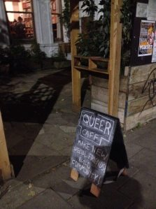 Queer cafe, make new special friends, build community, chalked blackboard on the pavement outside a house in the evening.