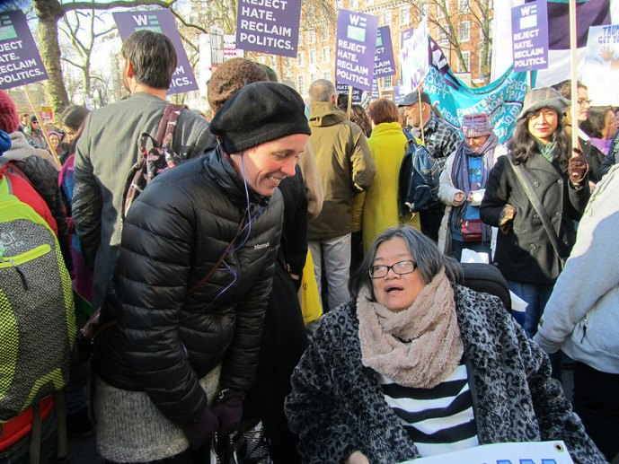 Caucasian woman speaking to a East asian woman wheelchair user with many women carrying placards behind them