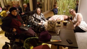 four women around a table, 2 wheelchair users, one with Middle Eastern, one with East Asian looks, the other Caucasian with one in a bed chair lying down position.