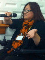 Eleanor, an East Asian woman, is holding a mic. Her left hand is extended and she has an orange scarf with black markings.