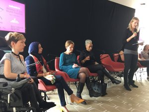 Women's panel with one white woman speaking into the mic. $ other seated women, one wheelchair user and one woman in a headscarf.