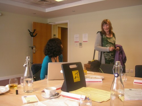 2 women, one looking away with her laptop in conversation with the other. There is a portable hearing loop on the table as well as bottles of water and tea cups.
