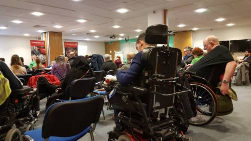 participants with backs to camera - some in wheelchairs away from the camera