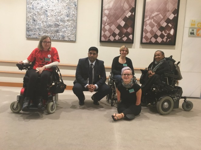 with man in a squatting position, 3 women wheelchair users and one woman in front.