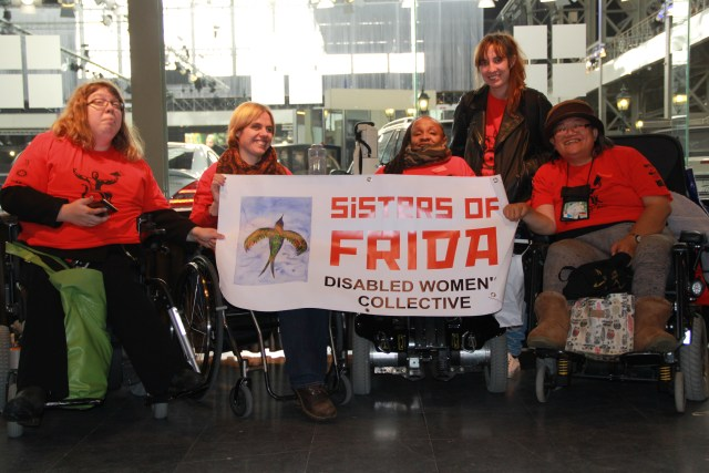 Sisters of Frida behind the banner which says Sisters of Frida, Disabled Women's Collective. They are all wearing read teeshirts. Four wheelchair users.