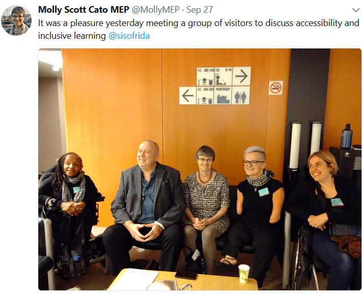 2 wheelchair users (one  black woman and one white) at either end. 3 people on sofa, all white, one man 2 women)