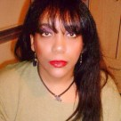A middle-aged Lenape and Nanticoke (Delaware) Native American woman who looks much younger than she actually is wearing an olive green shirt and an Amazonian necklace looks directly into the camera. Her large brown eyes and long brown hair with bangs / a fringe dominate the image.