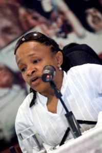 A Black woman in front of a mic who is wearing a white shirt