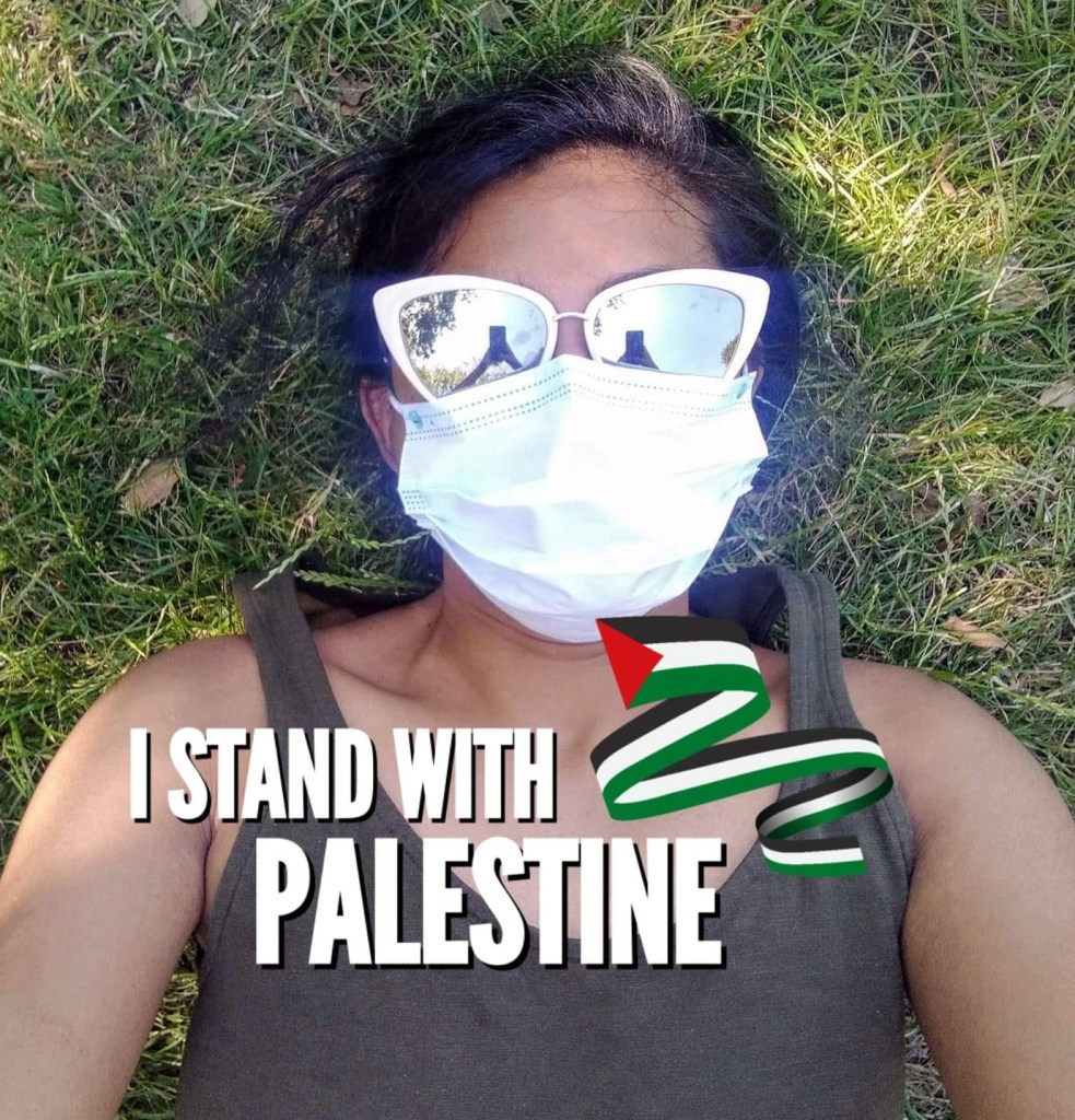 Brown woman with white rimmed glasses lying on grass. Text reads ''''I stand with Palestine'