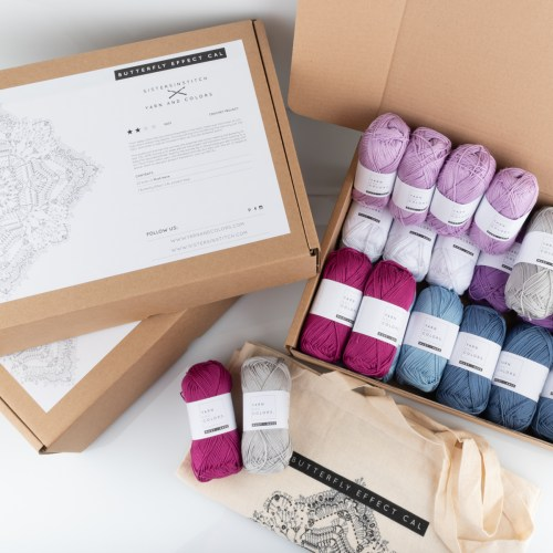 Three CAL yarn kit boxes with the The Butterfly Effect CAL 2019 in the BE future colorway placed on a white background. Yarn skeins in beautiful shades of lilacs, blues and greys.