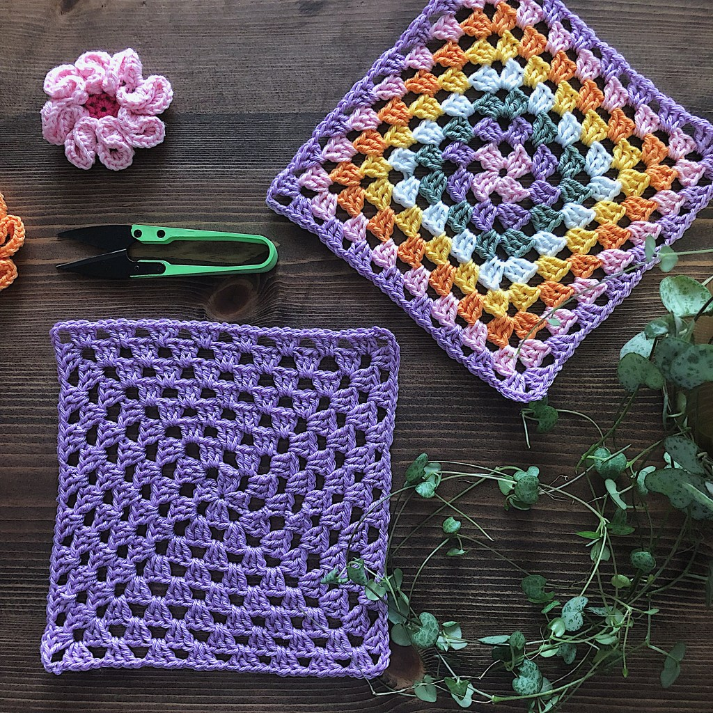 Two granny squares in Lilac and vibrant colors are placed on a dark wooden table with a crocheted flower and a scissor