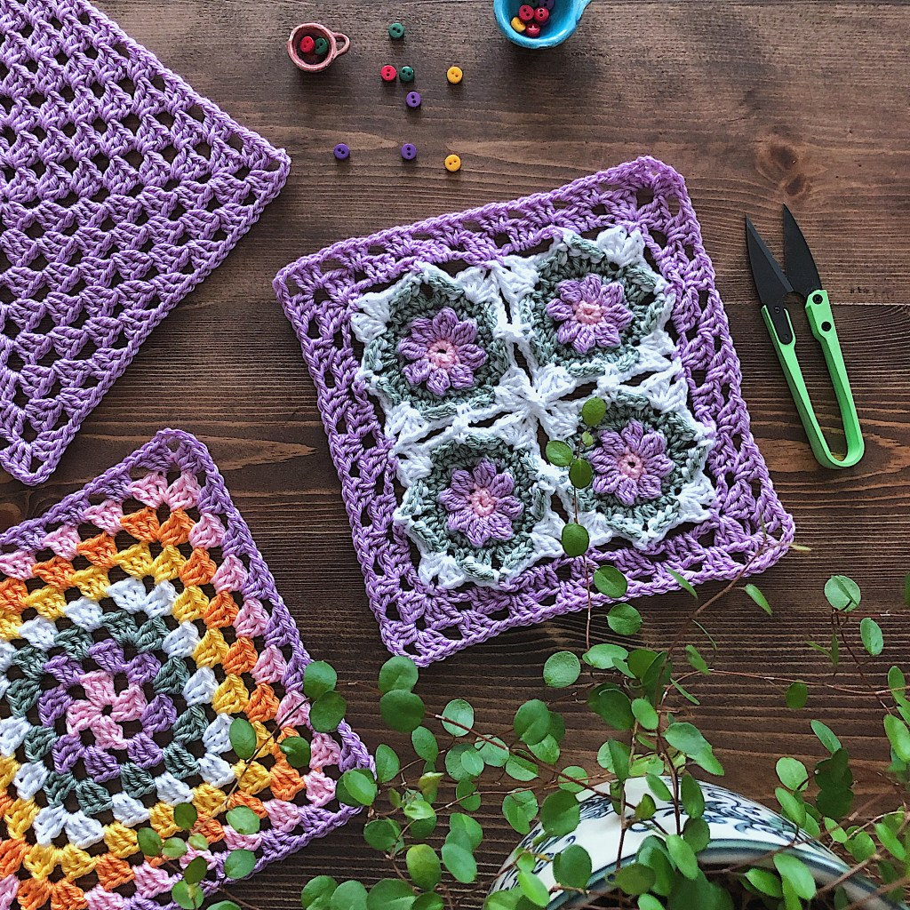 An After Effect Goes Granny Square placed on a dark wooden table with green leaves and crochet tools