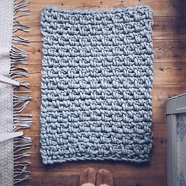 A chunky light grey Emilia blanket is placed on a raw wooden floor with slippers and some rug tassels framing the picture