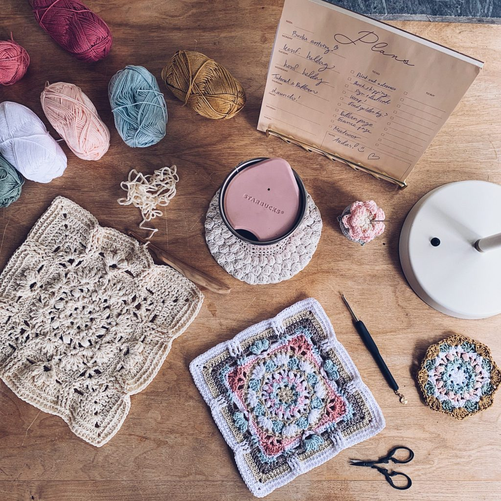 A finished solid coloured Patch of poises squares lays on a working table together with the original and lots of crochet tools and yarn