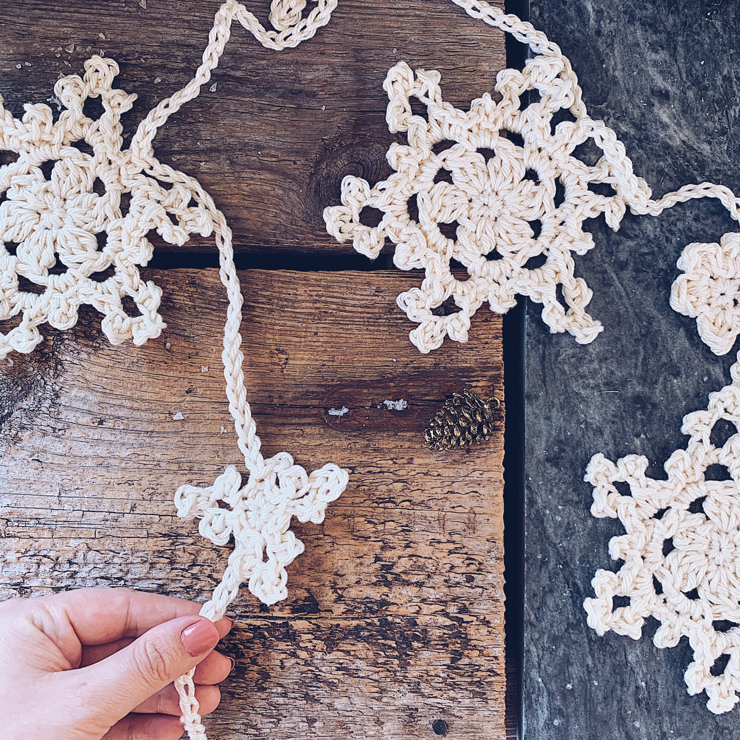 A crocheted Winter In Bloom Bunting in a soft cream colour draped over a wooden background