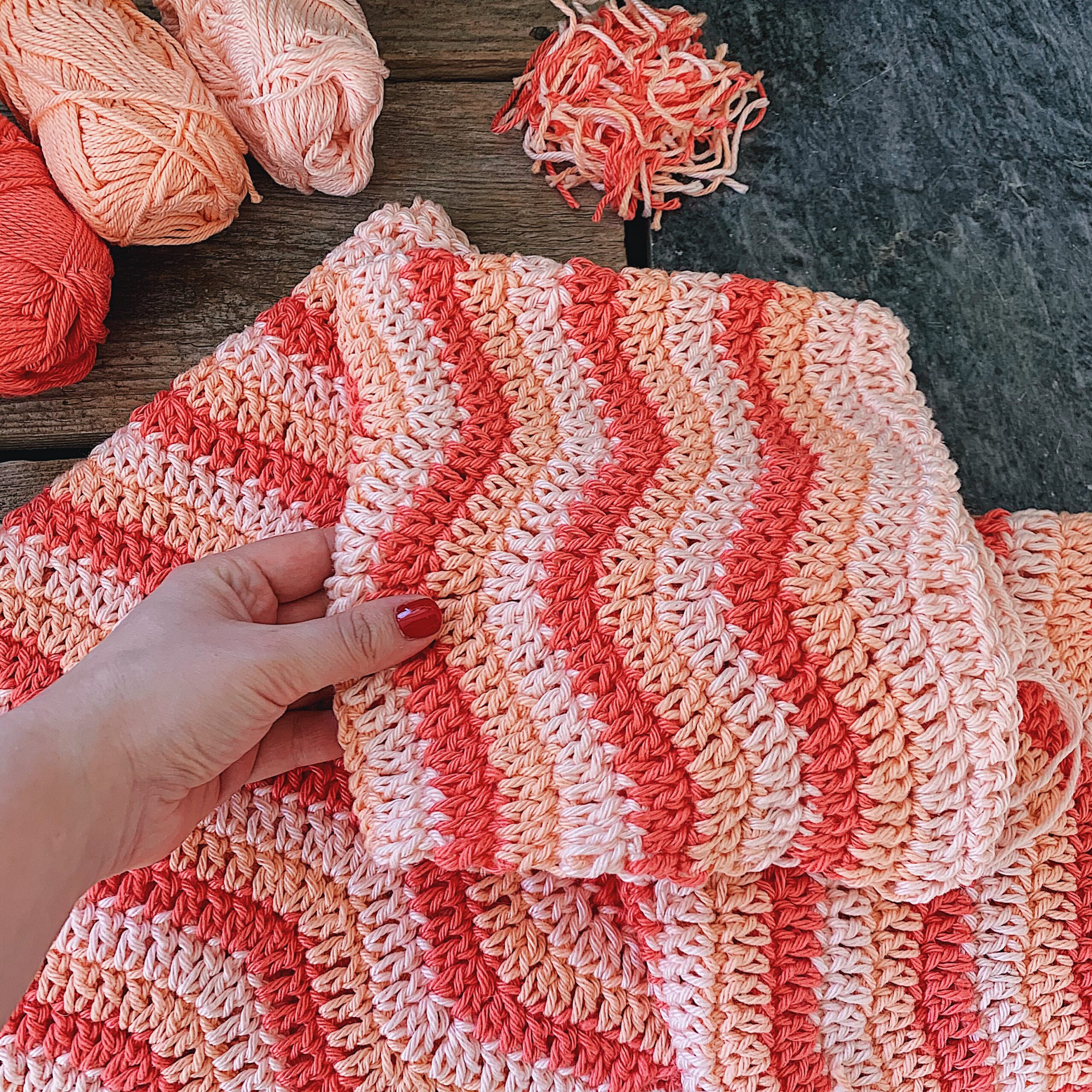 A closeup of the Malibu Sweater as a work in progress, pink and peachy shades in a wave pattern