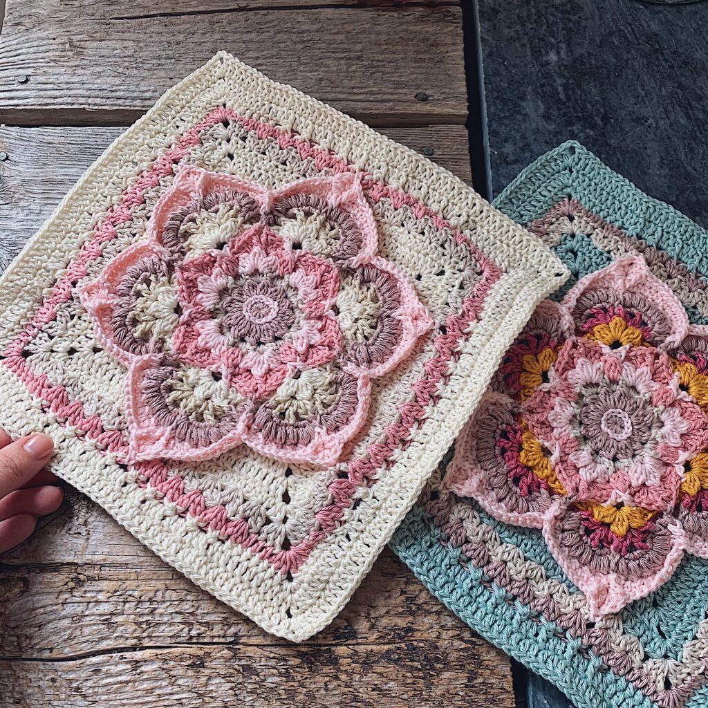 Two Blooming Lotus Squares in vintage pinks and teal tones placed on a table