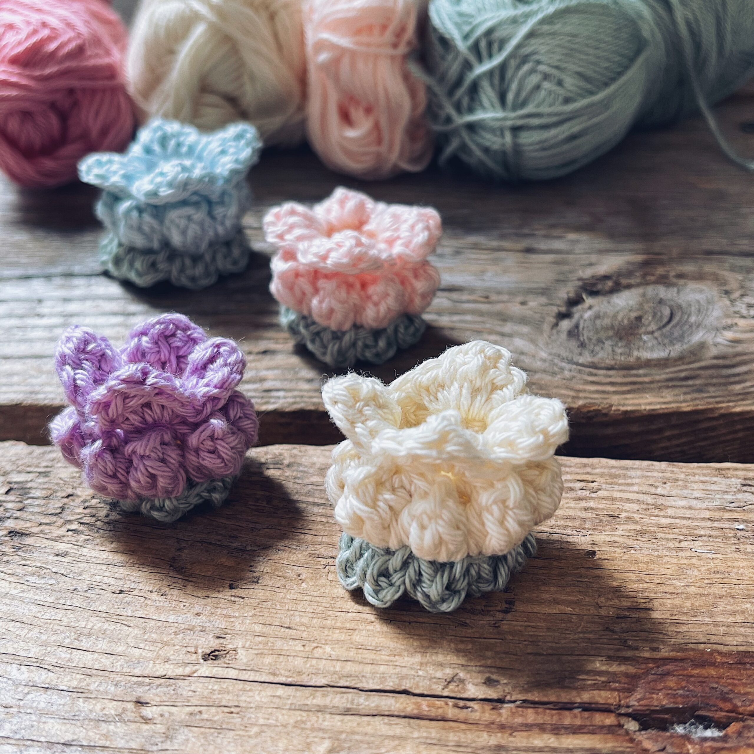 Four Poppy Pod Flowers in white, lilac, pink and blue colors placed on a wooden background together with yarn skeins