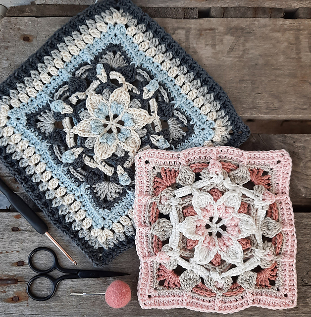 Two overlay textured squares in pinks and blues are placed on a table together with a crochet hook and a scissor