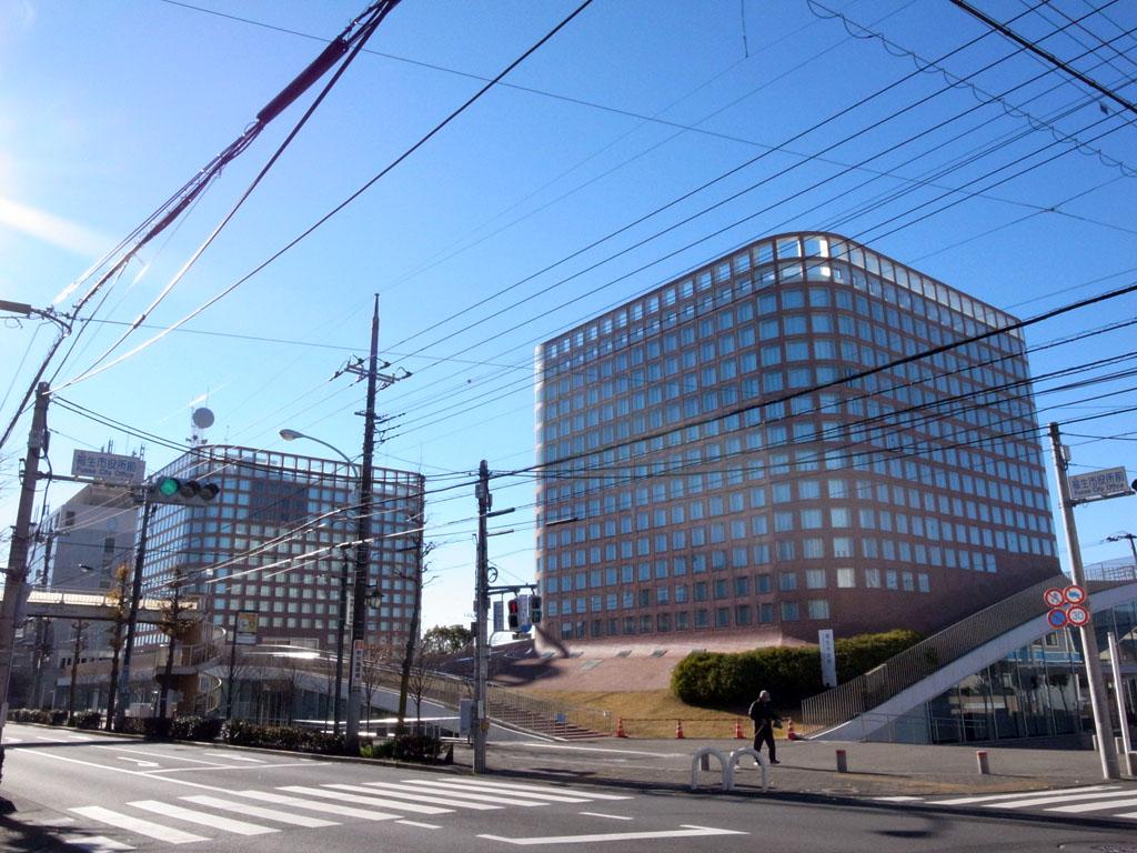 "JR青梅線福生駅から徒歩約5分の場所にある福生市役所。凡庸な郊外の風景にあって一際目立つ2棟の斬新な建物は建築家・山本理顕によるもの。この庁舎建設には、基地に由来する交付金約6億円があてがわれたと<a href=""http://www.amazon.co.jp/基地はなぜ沖縄に集中しているのか-NHK取材班/dp/4140815019/?_encoding=UTF8&amp;camp=247&amp;creative=1211&amp;linkCode=ur2&amp;tag=sitebg0e-22"" target=""_blank"">『基地はなぜ沖縄に集中しているのか』</a><img style=""border: none !important; margin: 0px !important;"" src=""http://ir-jp.amazon-adsystem.com/e/ir?t=sitebg0e-22&amp;l=ur2&amp;o=9"" alt="""" width=""1"" height=""1"" border=""0"" />にある。(撮影=bg)"