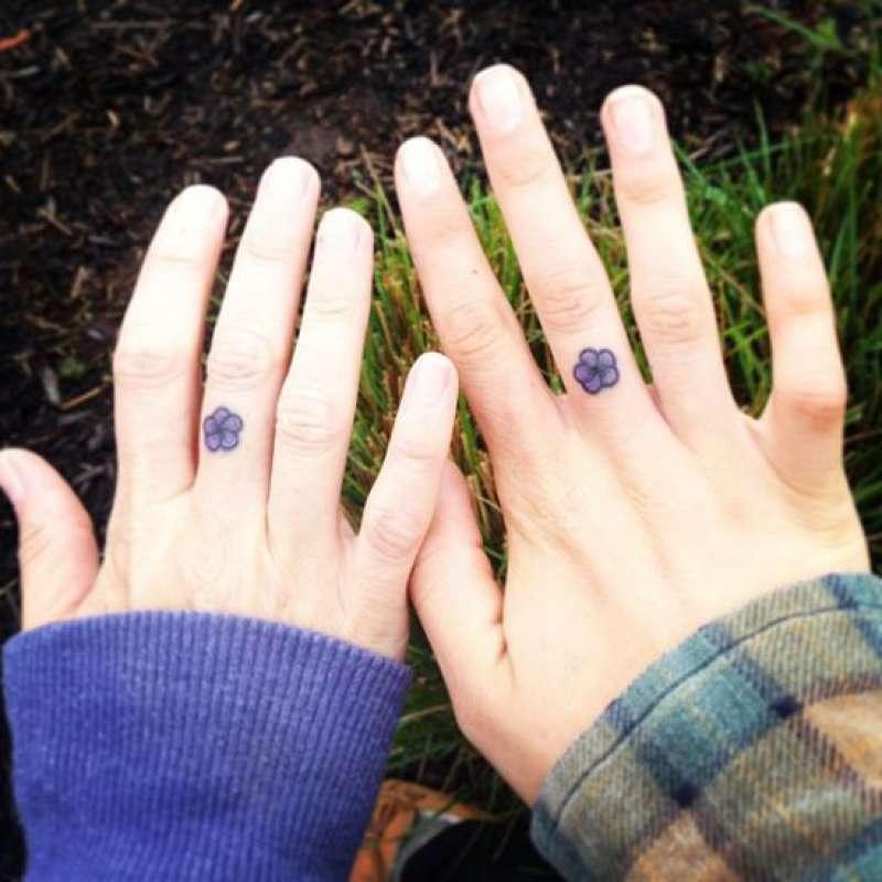 Mãos femininas tatuadas com flor