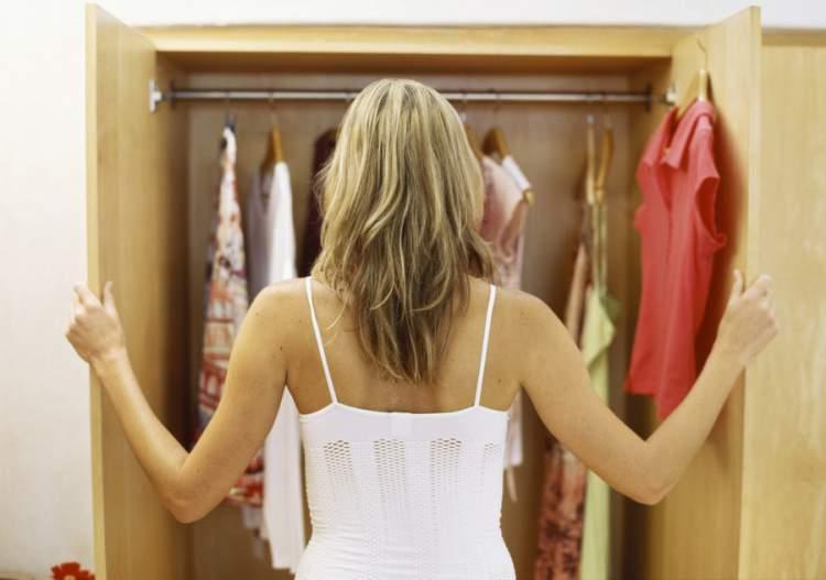 mulher olhando as opções de roupa dentro do seu armário