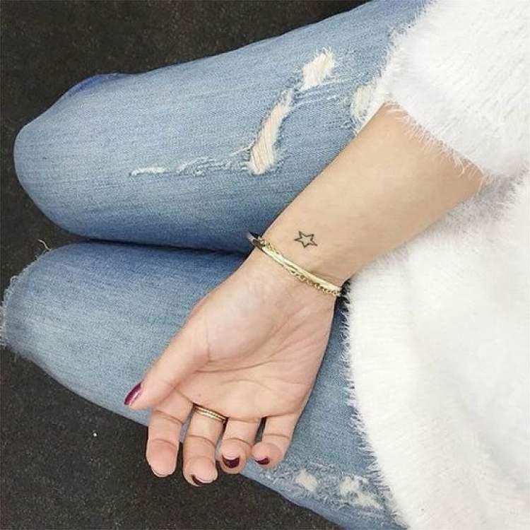 pequena estrela tatuada no punho