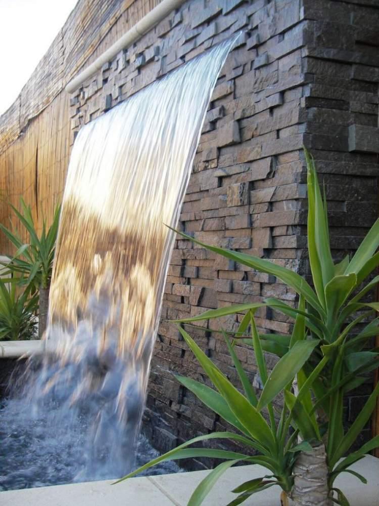 Fonte através de abertura na parede do jardim