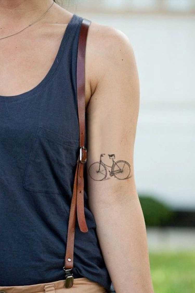 Tatuagem com o desenho de uma bicicleta no braço