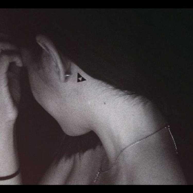 Tatuagem feminina delicada atrás da orelha com o desenho de um triângulo com outro triângulo invertido dentro