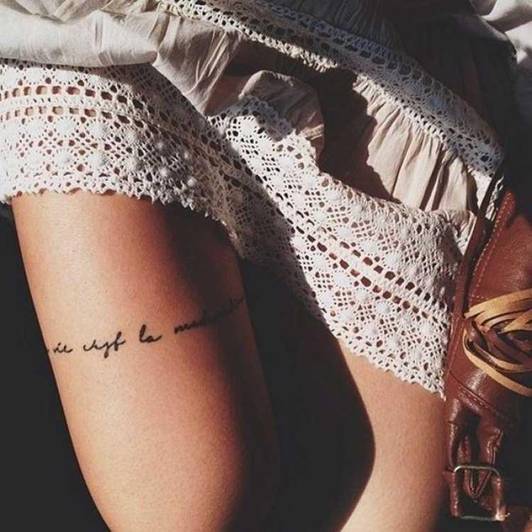 tatuagem feminina delicada com dizeres na coxa