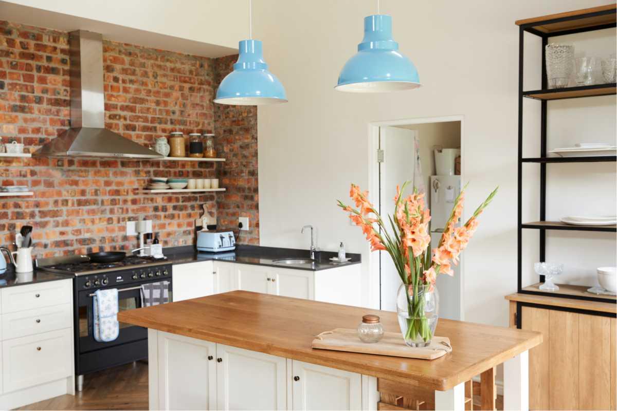 Cozinha com detalhes em madeira e luminárias azuis