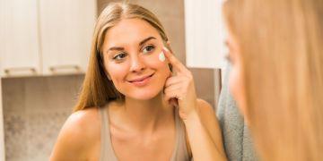 Jovem mulher na frente do espelho aplicando hidratante facial na pele oleosa.