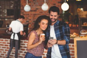 Smiling hipster couple looking at smartphone at coffee shop