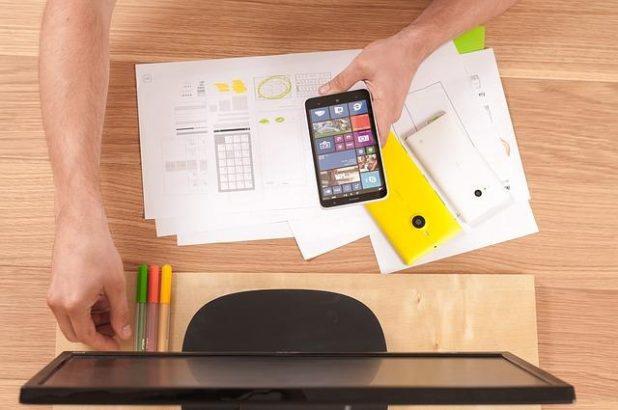 شخص يحمل هاتفًا محمولًا أمام الكمبيوتر.
