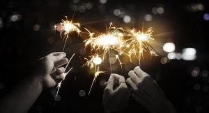a group of hands holding sparklers