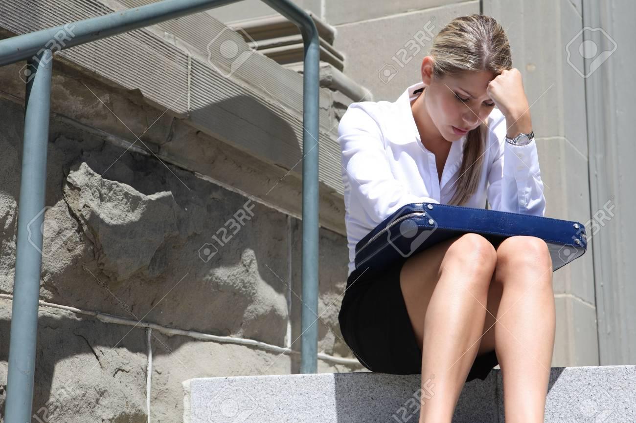 16496178-una-mujer-de-malestar-de-negocios-deprimido-que-se-sienta-fuera-de-la-empresa
