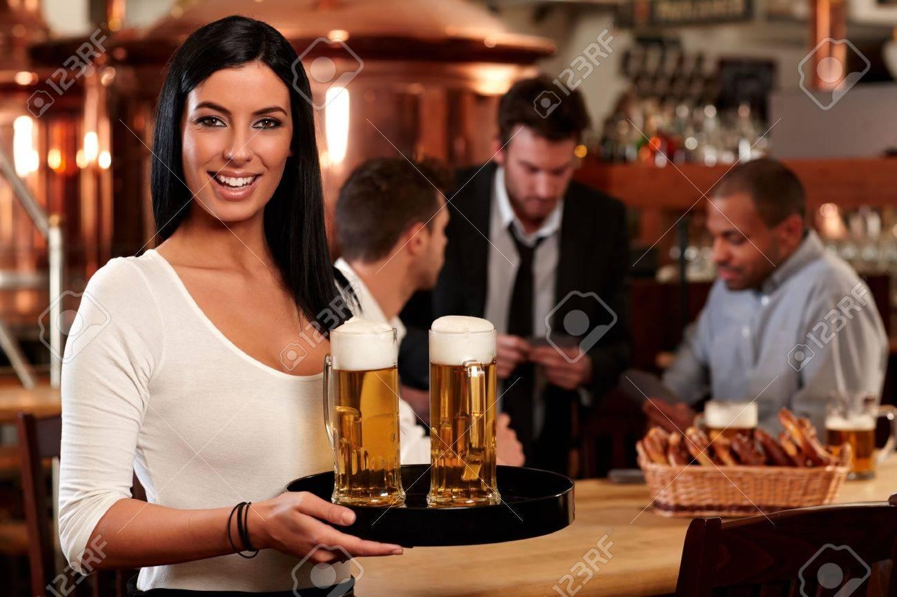 14821344-retrato-de-mujer-joven-y-feliz-de-servir-la-cerveza-en-el-bar-mirando-a-la-cámara-sonriendo-