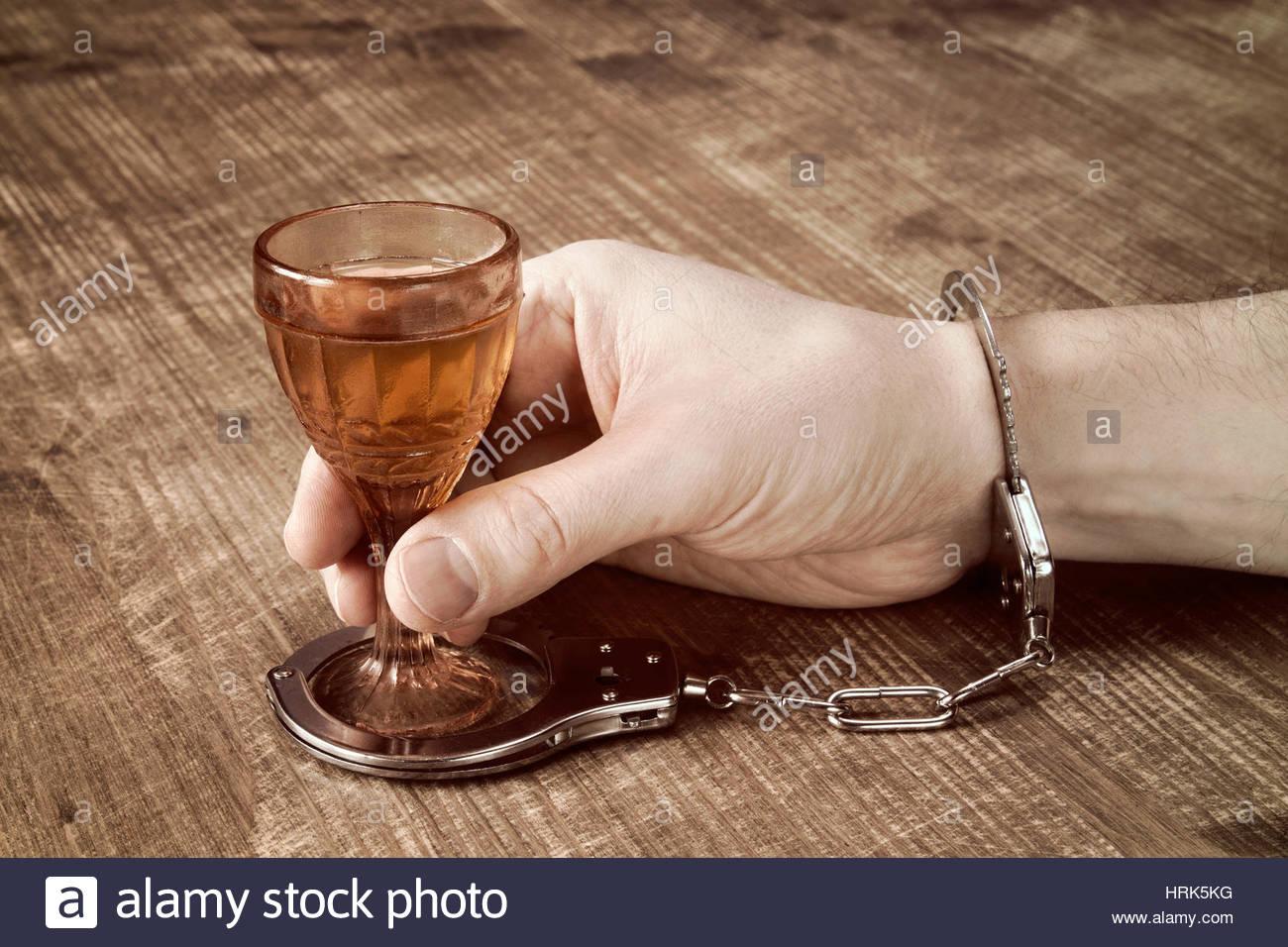 la-adiccion-al-alcohol-la-mano-esposado-con-un-vaso-de-alcohol-hrk5kg