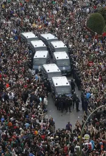 Los manifestantes rodean las furgonetas de la policía.
