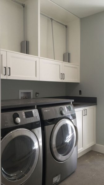 Laundry room with hanging space above