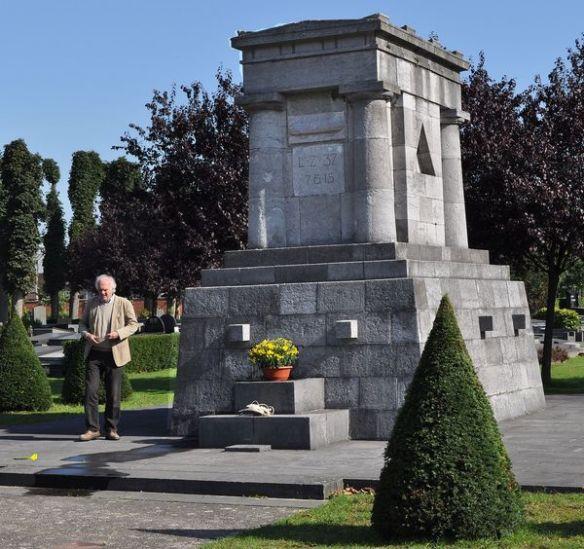 LZ 37-Denkmal auf dem Genter Westfriedhof. Hinter der Grab-Bodenplatte von Obltn. Otto van der Haegen (Inschrift eingraviert auf der Bodenplatte) steht der Enkel des ehemaligen  LZ 37-Maschinisten Carl Clauss, dessen Grab damals 1956 mit allen anderen deutschen Soldatengräbern aus WW I und WW II auf den deutschen Soldatenfriedhof in Vladslo umgebettet wurde.  Enkel Gert-Rücker (74) besuchte  gemeinsam mit  Autor Günter Dick aus Sankt Augustin im September 2010 das Erinnerungsdenkmal. Hierbei wurde auch die Idee für eine dort notwendige Informations-Tafel angeregt. Die Grabplatte von Kurt Ackermann-Berlin liegt verdeckt hinter dem Spitz-Buchsbaum. Foto: © Günter Dick